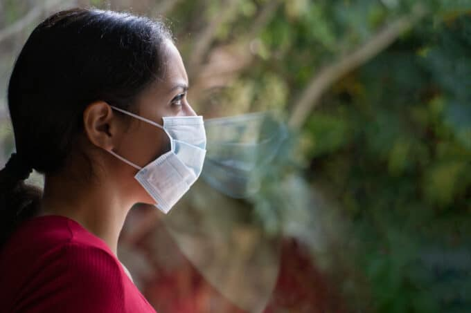 Woman wearing a face mask and looking unhappy because she wants a divorce during the coronavirus